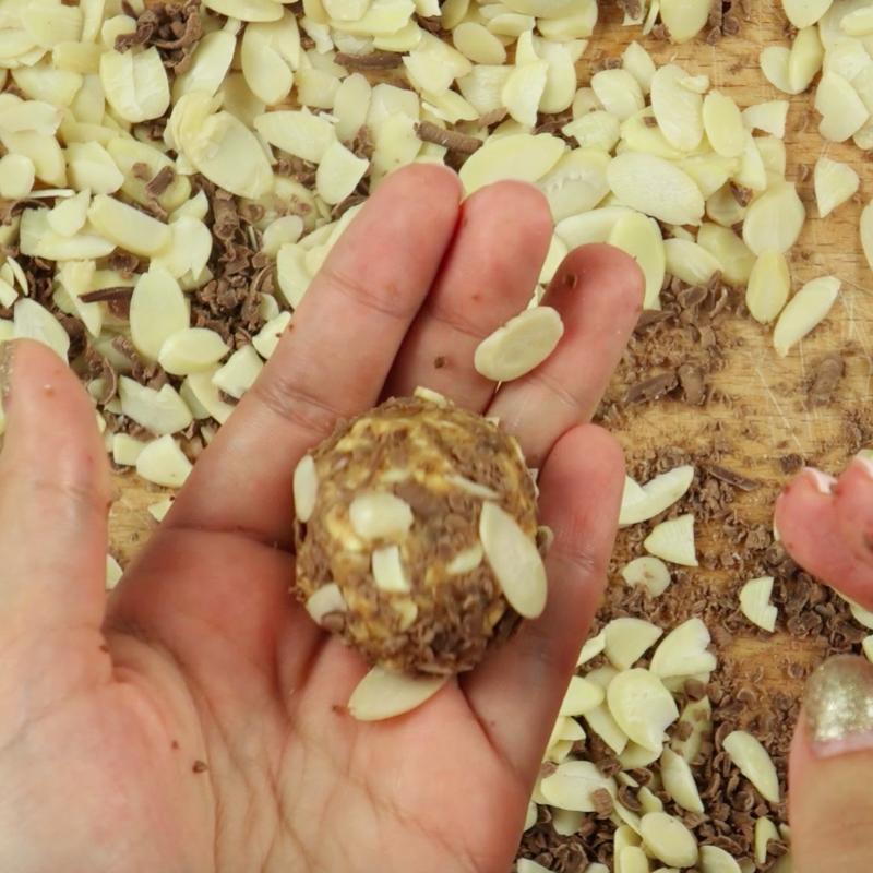 Na stole rozsyp pozostałą ilość startej czekolady oraz migdały w płatkach i przeturlaj w nich ulepione kulki tak, aby były pokryte z zewnątrz czekoladą oraz migdałami.