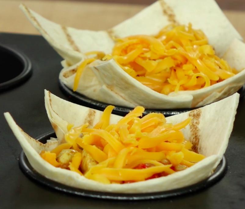 Do każdej foremki włóż po jednym kwadraciku tortilli. Następnie do każdego z nich włóż po ok. 1,5 łyżce farszu i 1 łyżce startego sera cheddar.