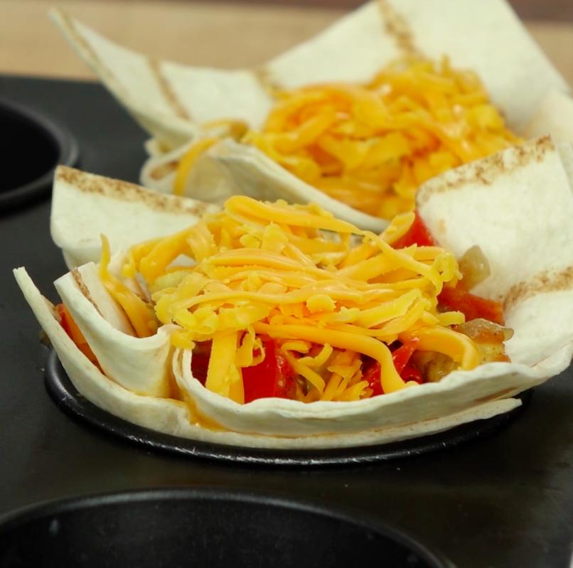 Następnie znów do każdej foremki włóż po kolejnym kwadraciku tortilli oraz po 1,5 łyżce farszu i 1 łyżce sera.