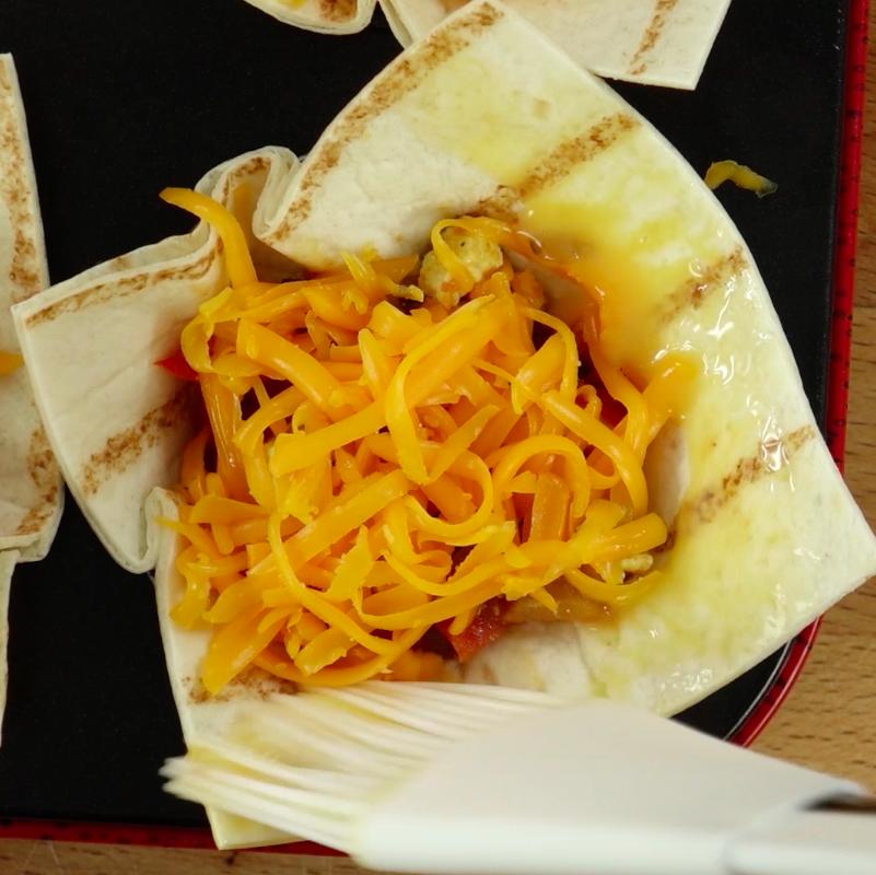Za pomocą pędzelka, wystające kawałki placków tortilli nasmaruj roztopionym masłem.