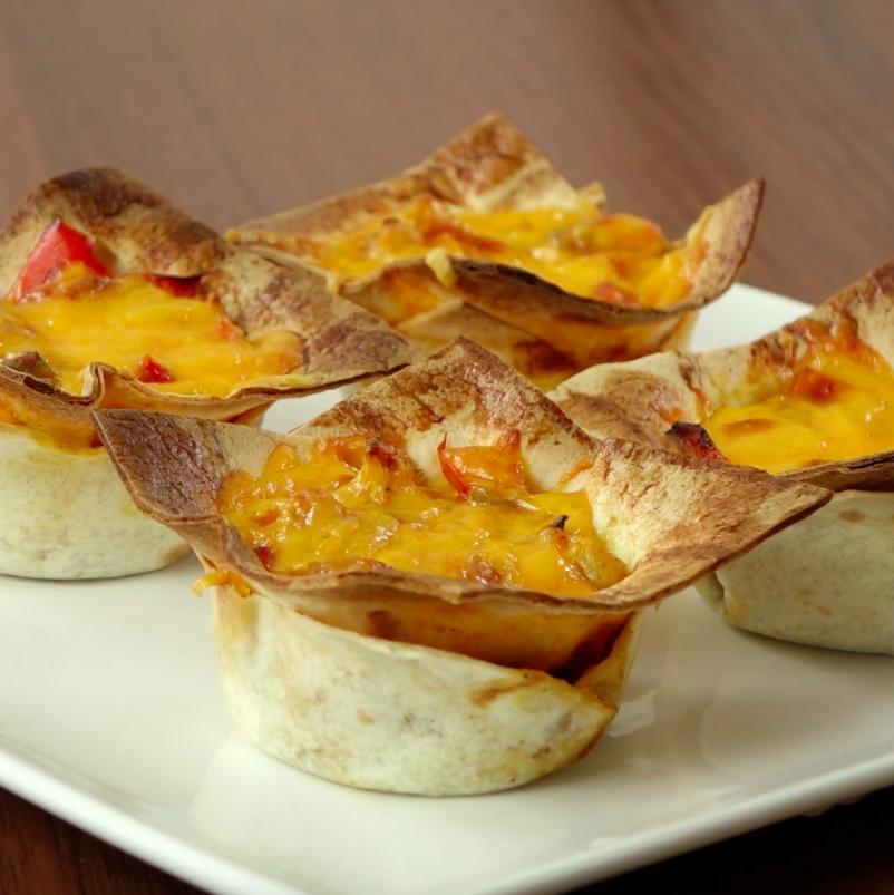 Po 20 minutach wyciągnij gotowe danie z piekarnika. Wyjmij tortille z foremek i połóż na talerzu. Jeżeli masz ochotę, możesz posmarować ich wierzch sosem pomidorowym oraz posypać świeżymi liśćmi pietruszki.