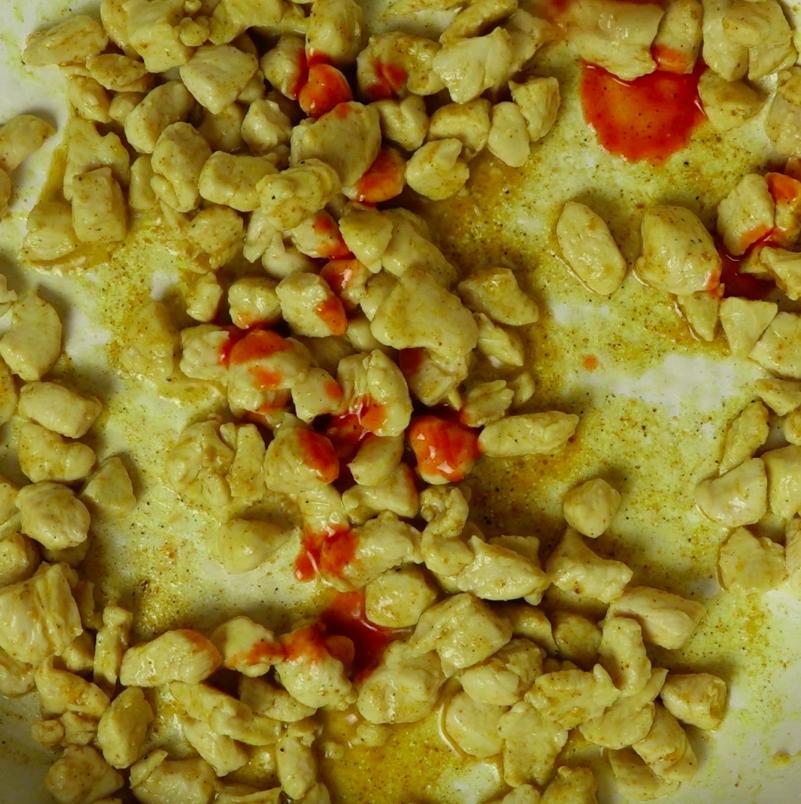 Dodaj do kurczaka sos chilli i dokładnie wymieszaj. Zdejmij patelnię z ognia.