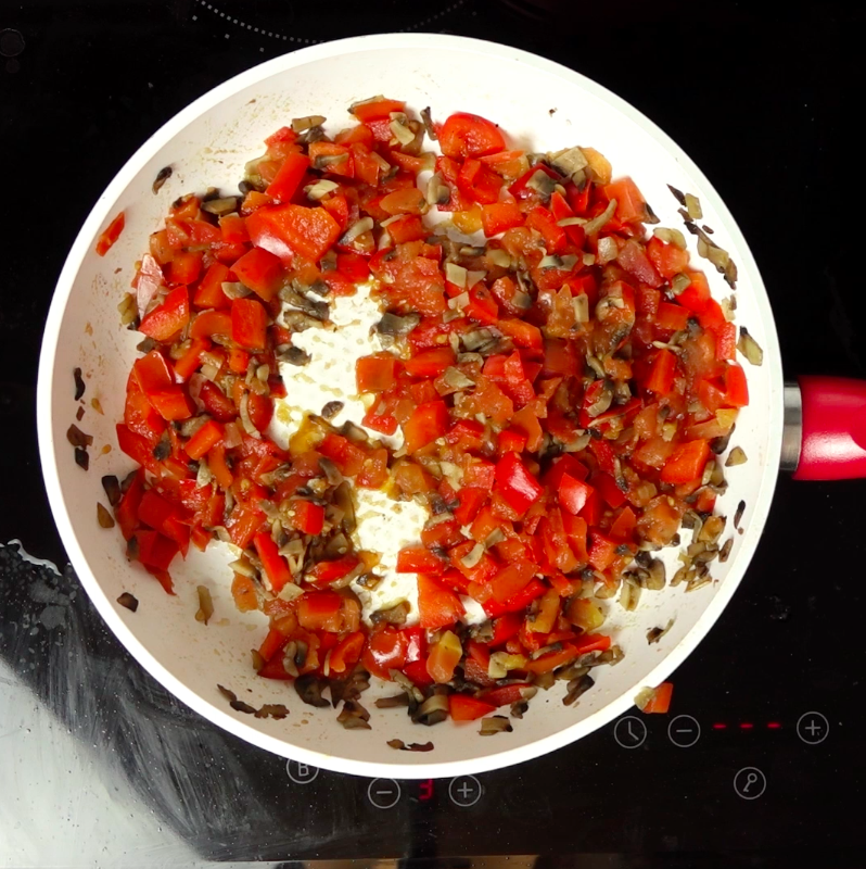 Na osobną patelnię wrzuć 20 g masła. Kiedy się rozpuści, dodaj pieczarki, cebulę, paprykę, pomidora. Przypraw solą i pieprzem i dokładnie wszystko wymieszaj.