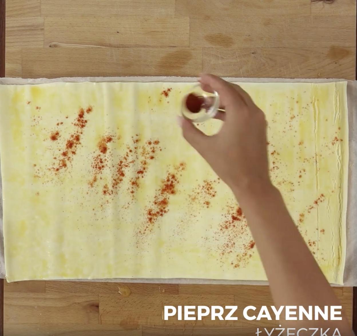 Rozwiń ciasta francuskie i za pomocą pędzelka nasmaruj je jajkiem. Następnie posyp jego wierzch pieprzem cayenne.