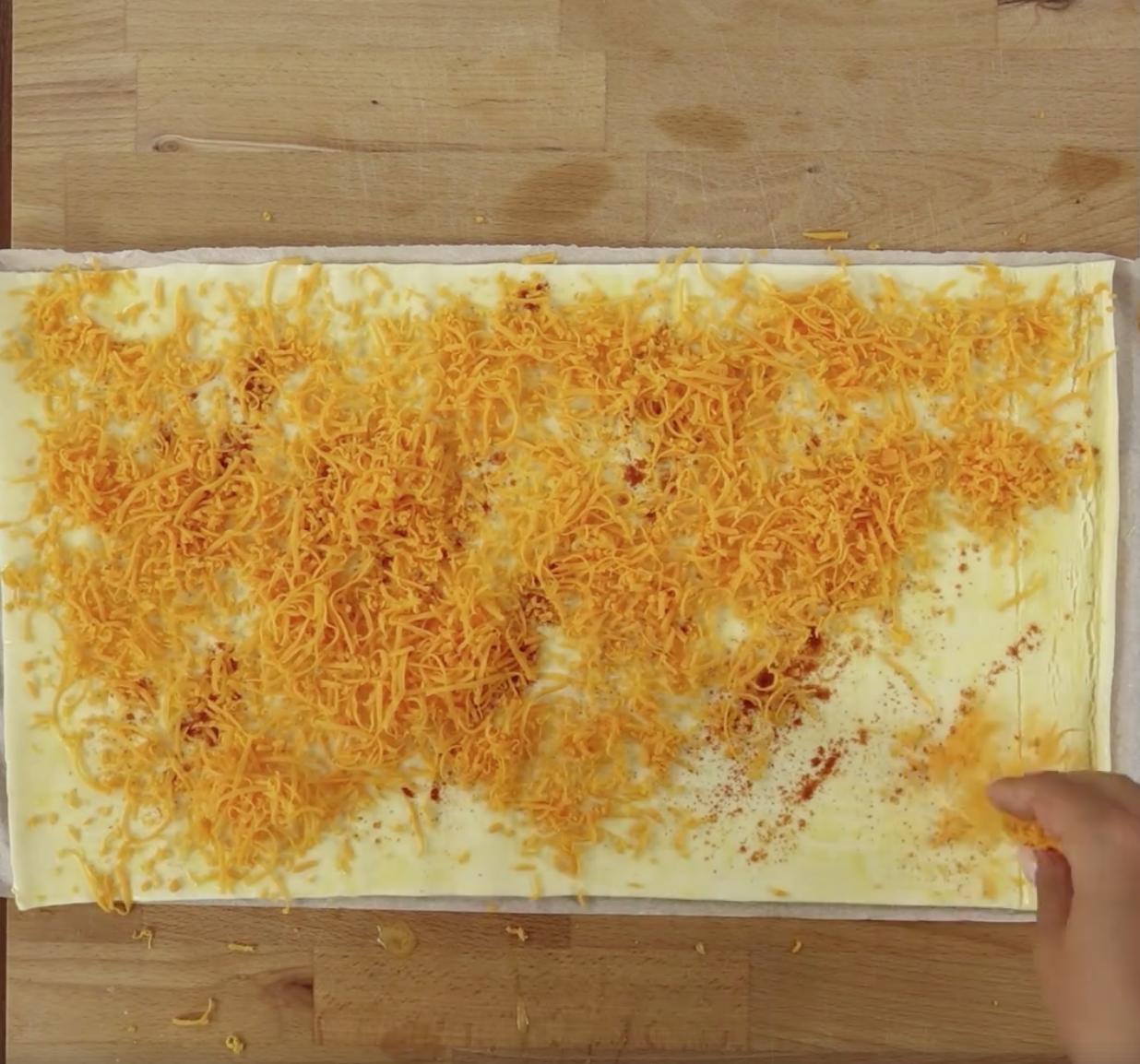 Równomiernie posyp ciasto francuskie startym serem cheddar.