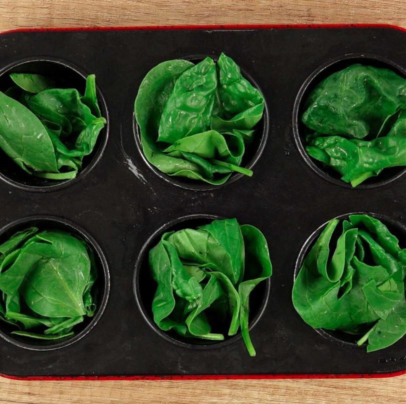 Rozłóż liście szpinaku pomiędzy 6 foremek i delikatnie je ugnieć.
