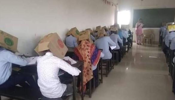 studenci z pudłami na głowie